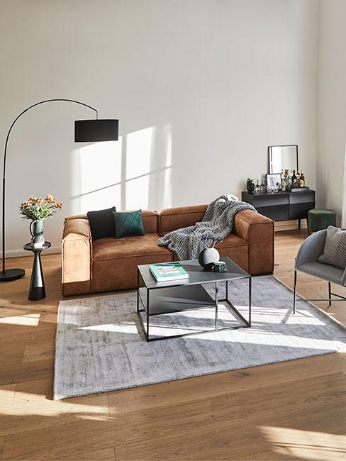 duży salon z modułową sofą z brązowej skóry i zielonymi poduszkami oraz czarną lampą w kształcie łuku