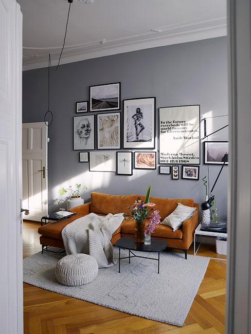 Mały salon z musztardową sofą narożną na tle szarej ściany z galerią grafik