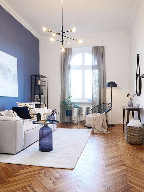 Salonw kamienicy z niebieską ścianą i popielatą sofą modułową oraz niebieskimi meblami