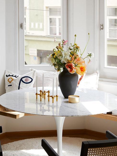 biały okrągły stół z marmurowym blatem przy wnęce okiennej z czarnym wazonem z kamionki