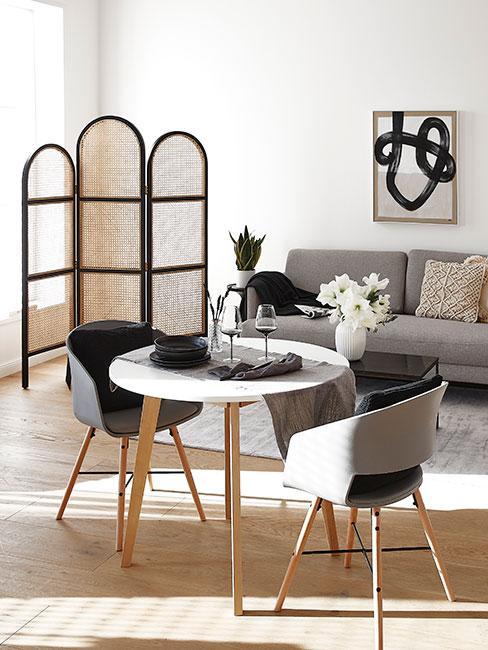 nowoczesna jadalnia z małym okrągłym stołem w salonie i parawanem z plecionki wiedeńskiej