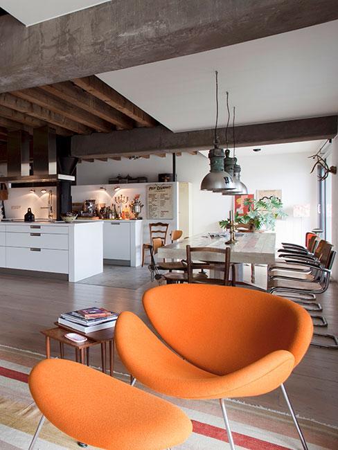 zbliżenie na nowoczesne pomarańczowe krzesło na tle białej industrialnej kuchni i jadalni z pofabrycznymi lampami w lofcie