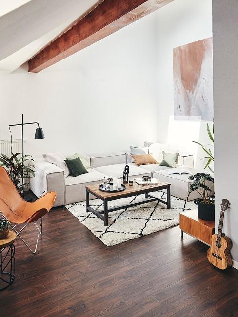 jasny salon z jasną sofą modułową, skórzanym fotelem motylem z belkami na na sufice