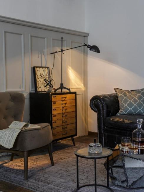 industrialny salon w ciemnych kolorach ze skórzaną sofą chesterfield