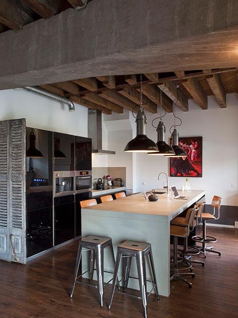 industrialna kuchnia w lofcie z belkami na suficie i metalowymi lampami