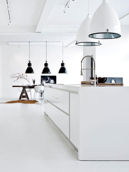 biała kuchnia z wyspą w lofcie, w tle jadalnia z drewnianym stołem i czarnymi industrialnymi lampami