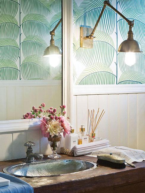 łazienka w stylu industrialnym z metalową lampą i zieloną tapetą