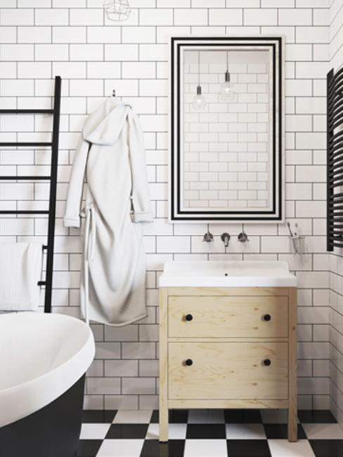 łazinek az białymi kafelkami w kształcie cegły i białoczarną podłogą, na której stoi czarna wanna