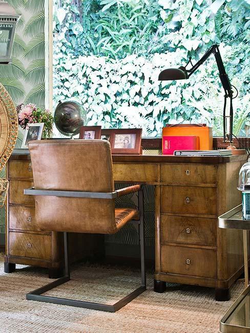biurko w stylu industrialnym ze skórzanym fotelem i zeiloną tapetą