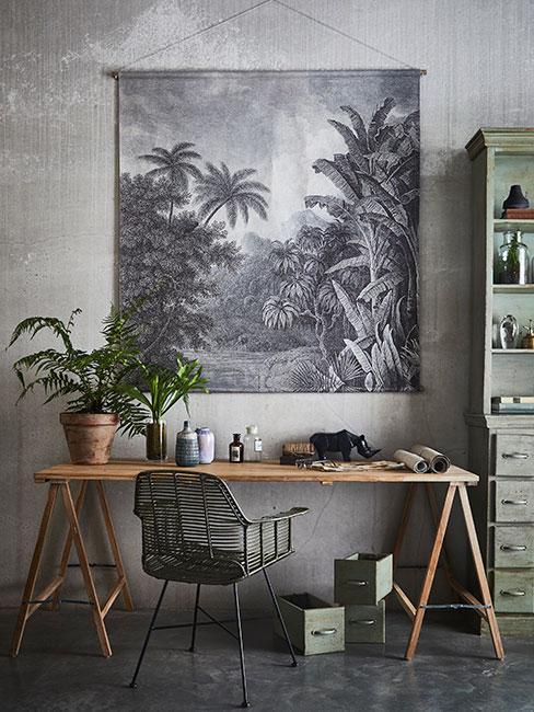 biurko w stylu industrialnym na tle szarego plakatu z rysunkiem dżungli