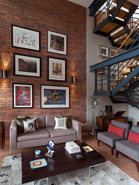 salon w lofcie z obrazami na ścianie z cegły