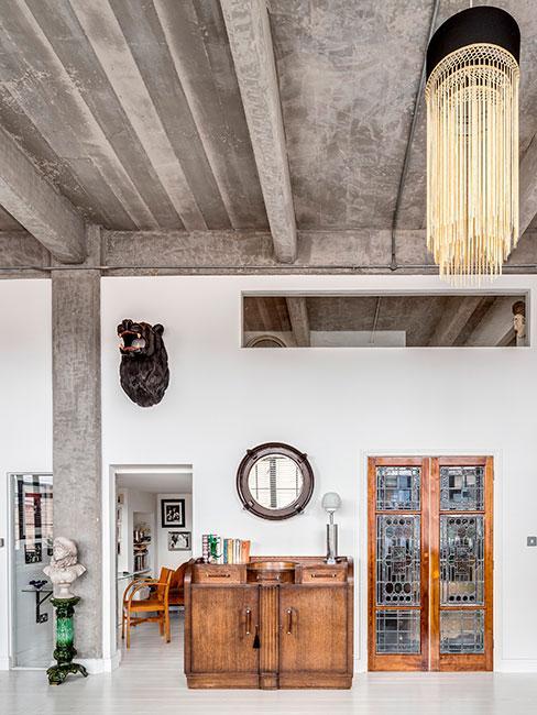przestrzeń loftowa z betonowym sufitem i dekoracjami etnicznymi