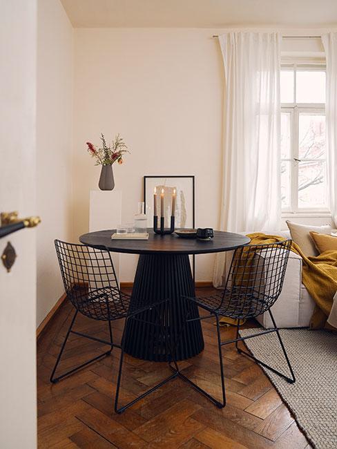 nowoczesna jadalnia z czarnym okrągłym stołem i ażurowymi krzesłami