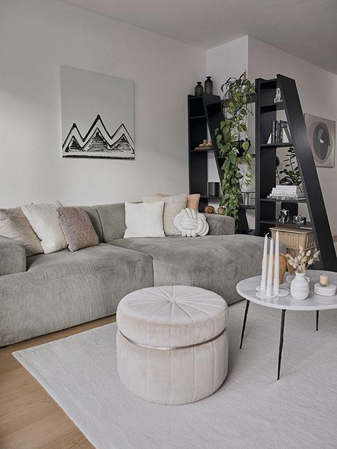 nowoczesny salon w bloku z szarą sofą modułową i czarnym regałem