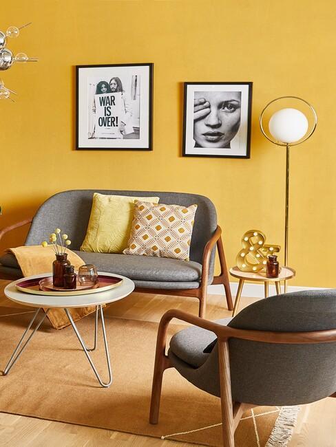 salon z żółta ścianą i szrą sofą