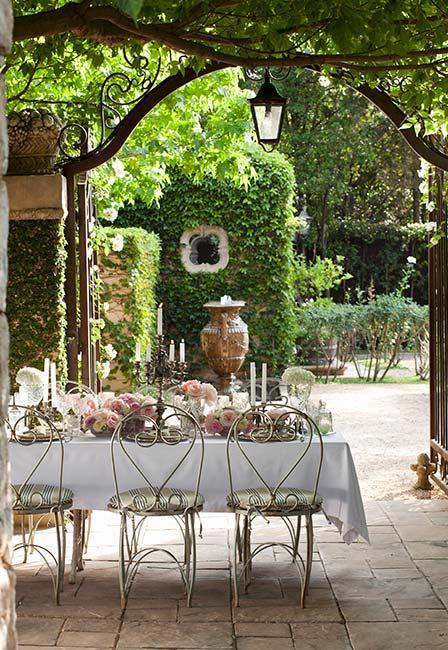 toskański ogród z metalowym stołem ogrodowym