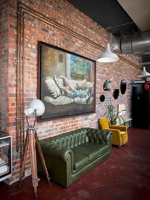 zielona sofa Chesterfield na tle ceglanej ściany w stylu industrialnym