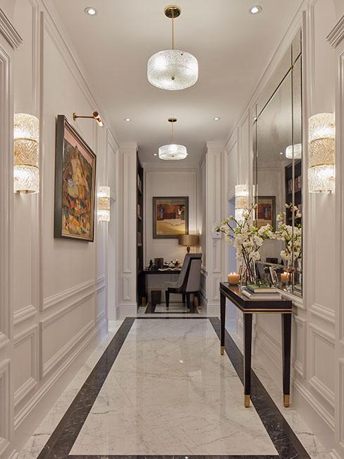 wąski przedpokój z podłogą z imitacji marmuru i dużym lustrem w sytlu art deco