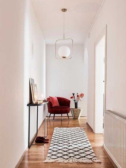 Wąski przedpokój z dywanem oraz burgundowym krzesłem i wazonem
