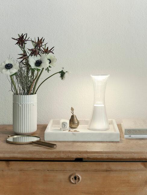 Kwiaty i lampka stojące na szafce w przedpokoju