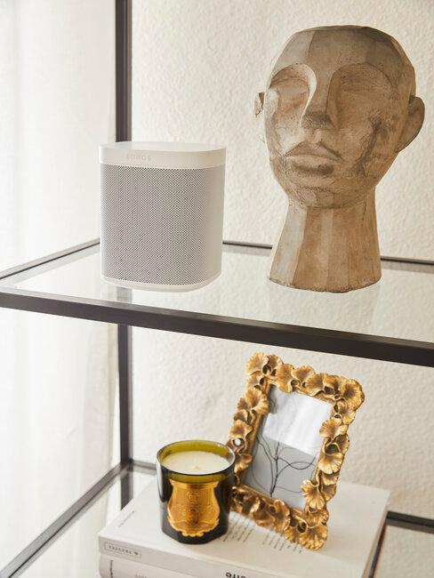 Półka z rzeźbami i ramkami w przedpokoju