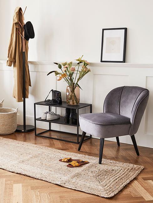 klasyczny przedpokój z lamperią, czarną konsolą i szarym tapicerowanym krzesłem z aksamitu
