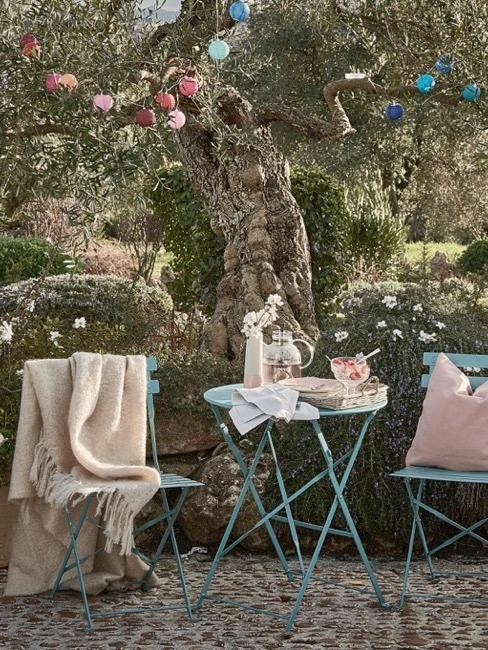 Mały estetycznie zaaranżowany ogród, stoliki pod drzewem