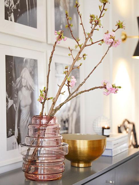 rożowy szklany wazon z gałązkami wiśni na komodzie z galerią czarnobiałych zdjęć w tle