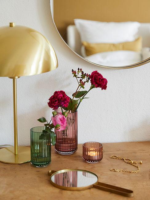 złota lampa obok lusterka i szklanych wazpnów na drewnianej komodzie