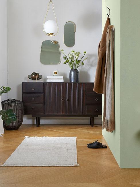 Klasyczny przedpokój z komodą z ciemnego drewna, lustrami w złotych ramach obok zielonej ściany