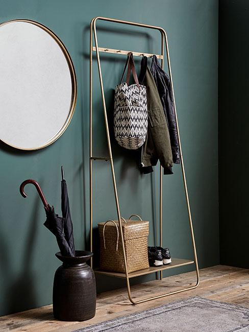 złoty stojak na ubrania obok ciemnego wazonu z parasolami na tle zielonej buetelkowej ściany
