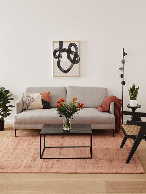 Salon z szarą sofą i tekstyliami w ciepłych barwach