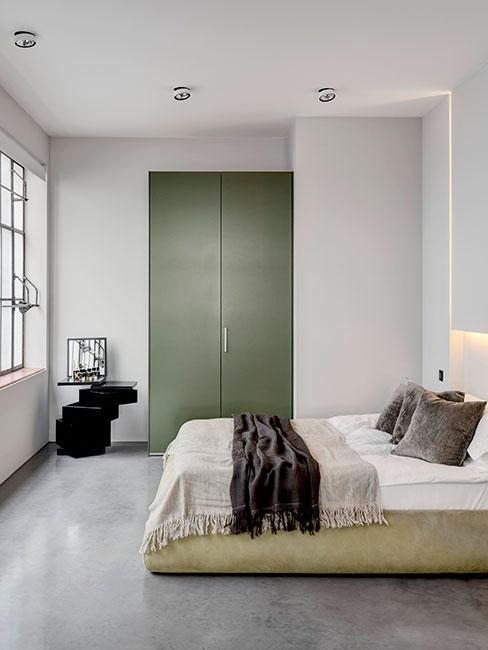 Nowoczesna sypialnia loftowa z oliwkową szafą i nowoczesnym czarnym stolikiem