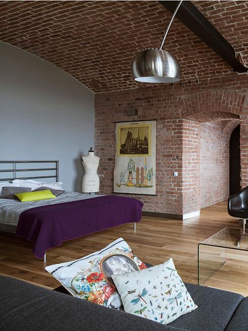 sypialnia w salonie we wnętrzy industrialnym w cegle