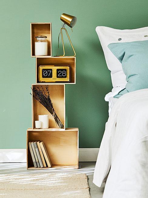 szafka nocna zrobiona ze skrzynek na tle zielonej ściany
