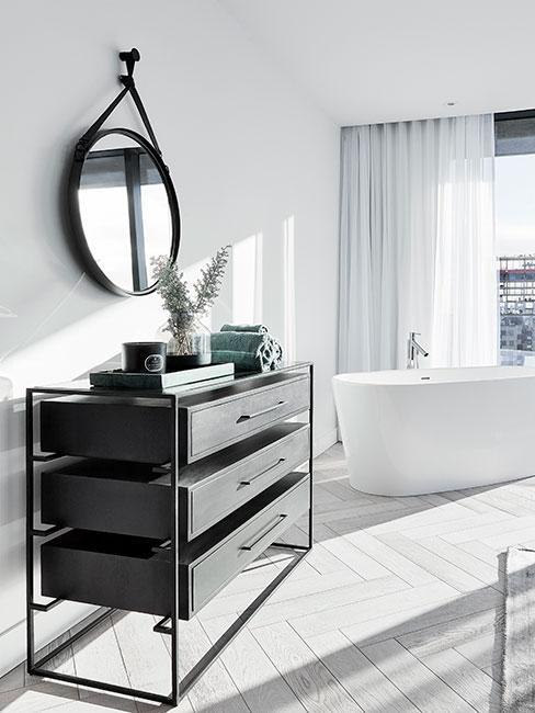 duża luksusowa łazienka z białą wanną wolnostojącą i czarną komodą
