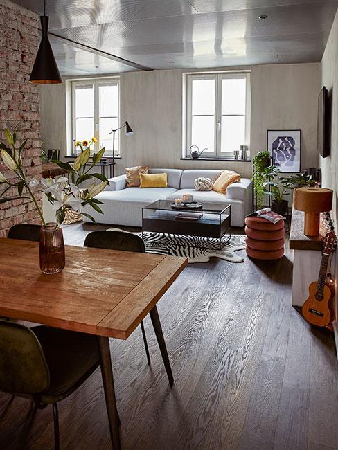 mieszkanie w stylu industrialnym z szarą sofą