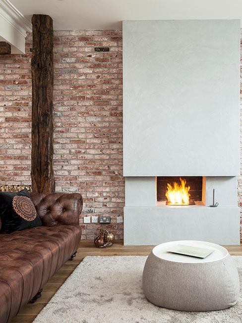 kominek w mieszkaniu loft obok brązowej sofy ze skóry