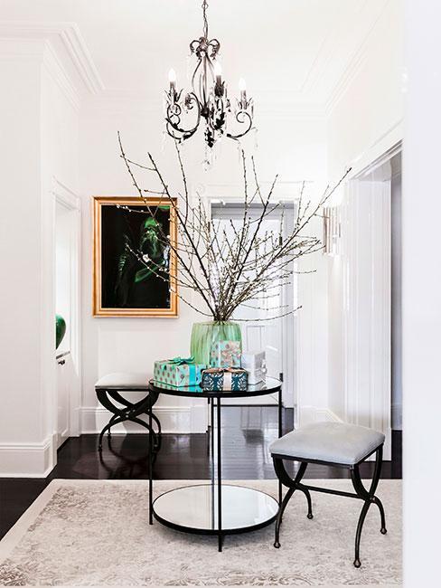 Przedpokój ze stolikiem pośrodku, obok dwa siedziska, wazon na stole