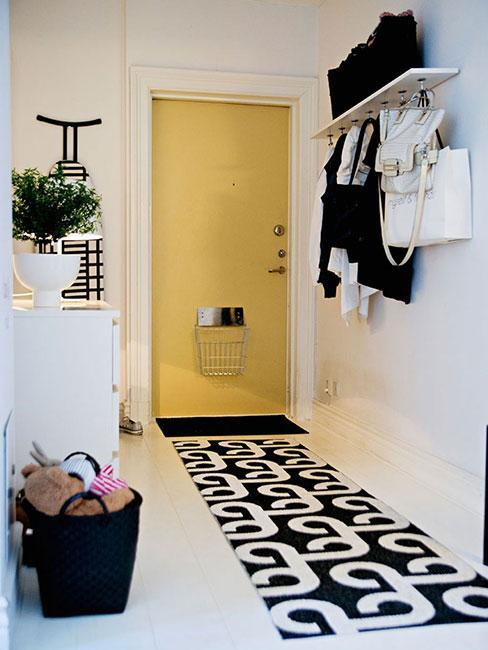 Przedpokój z dywanem w geometryczne wzory i żółtymi drzwiami