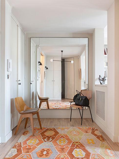 Przestronny przedpokój z dywanem i drewnianymi krzesłami