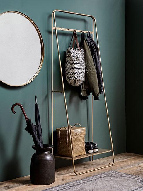 Przedpokój z ciemnozielonymi ścianami, stojakiem na parasolki i lustrem