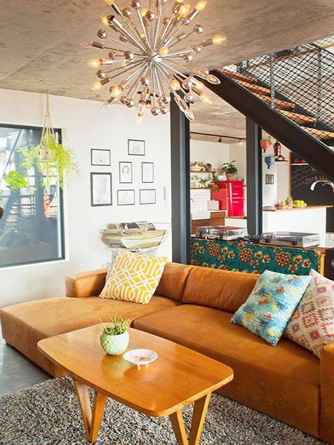 loft z brązową skórzaną sofą i okazałym żyrandolem
