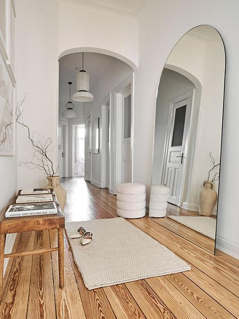 Przedpokój z dywanem w centrum i drewnianą półką przy ścianie
