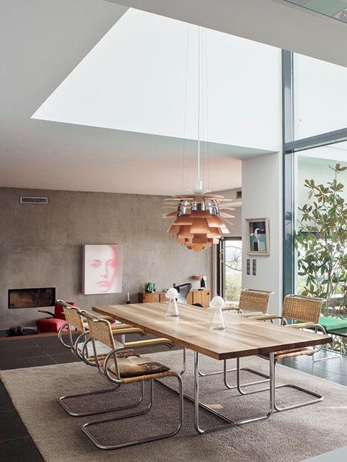 nowoczesna jadalnia w lofcie z dużym drewnianym stołem i nowoczesną miedzianą lampą