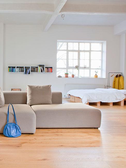 przestronny loft z szarą sofą modułową i łóżkiem z palet