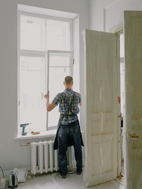 Mężczyzna wymienia okno w remontowanym mieszkaniu
