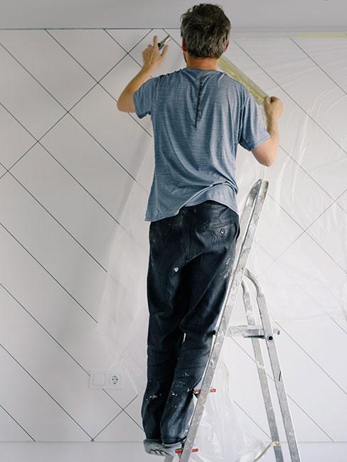 Pracownik na drabinie remontujący ścianę