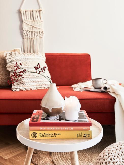 Salon z bordową kanapą, książki ułożone na stoliku