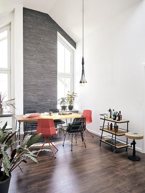 industrialna jadalnia w lofcie z szarą cegłą i drewnianym stołem na metalowych nogach oraz różnymi nowoczesnymi krzesłami